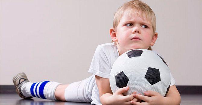 Ребенок отдыхает с футбольным мячом