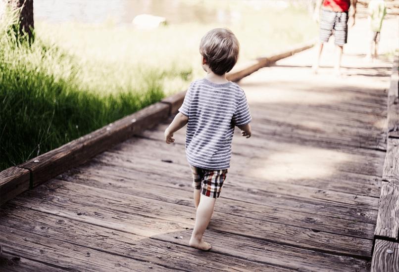 Босой ребенок идет к родителям